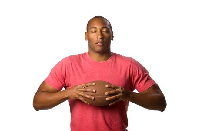 Football player holding a football with his eyes closed in contemplation.